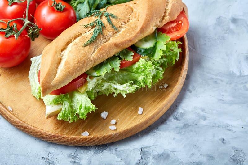 Το φρέσκο σάντουιτς με το μαρούλι, τις ντομάτες και το τυρί εξυπηρέτησε στο ξύλινο πιάτο πέρα από το άσπρο κατασκευασμένο υπόβαθρ στοκ φωτογραφία με δικαίωμα ελεύθερης χρήσης