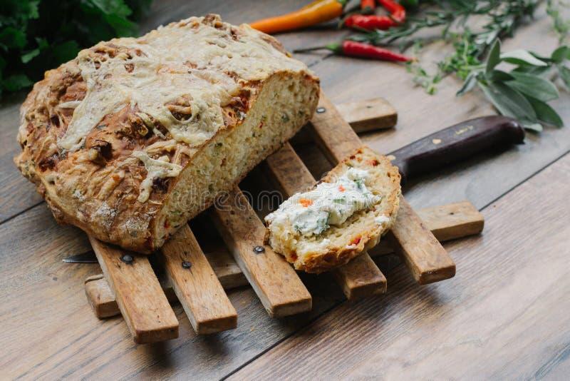 Το φρέσκο, σπιτικό ψωμί σε ένα ξύλινο πιάτο και μια φέτα του σπιτικού ψωμιού με το τυρί κρέμας έκαναν με το βούτυρο στοκ φωτογραφία με δικαίωμα ελεύθερης χρήσης