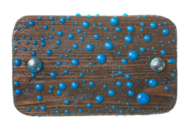 Το φυσικό πλαίσιο έκανε από τη σανίδα με τα μπουλόνια μετάλλων στις πτώσεις του μπλε χρώματος απομονωμένος στοκ εικόνα με δικαίωμα ελεύθερης χρήσης