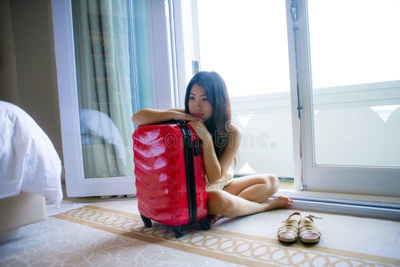 Το φυσικό πορτρέτο τρόπου ζωής της νέας ευτυχούς και όμορφης ασιατικής κινεζικής γυναίκας τουριστών με τη βαλίτσα ταξιδιού που φθ στοκ εικόνα