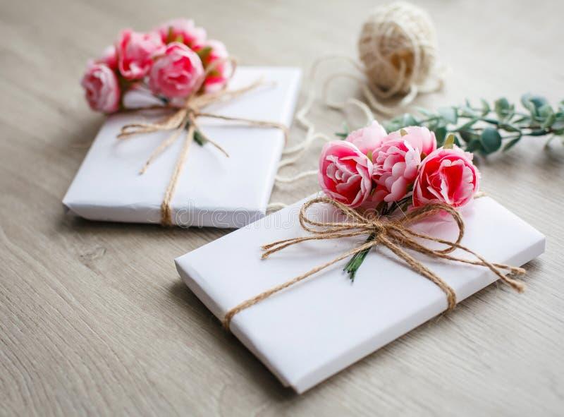 Το φυσικό ύφος το κιβώτιο δώρων στον ξύλινο πίνακα Χειροποίητο παρόν κιβώτιο που τυλίγεται στη Λευκή Βίβλο Floral στοιχεία ντεκόρ στοκ φωτογραφία με δικαίωμα ελεύθερης χρήσης
