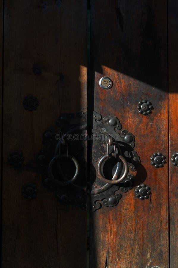 Το φως και η σκιά στις κορεατικές ξύλινες επιτροπές πορτών διακόσμησαν με τις παλαιές μαύρες μεταλλικές λαβές δαχτυλιδιών σε ένα  στοκ εικόνα με δικαίωμα ελεύθερης χρήσης