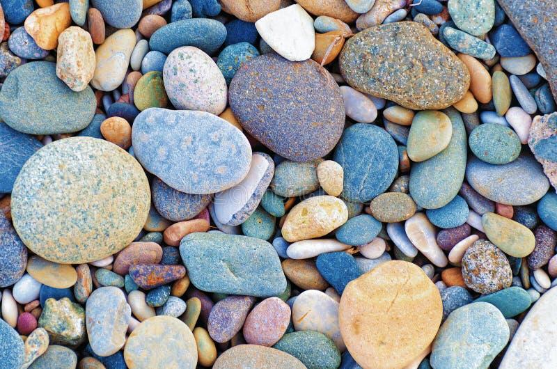 Το φωτεινό υπόβαθρο των πολύχρωμων στρογγυλών πετρών, χαλίκια θάλασσας, κλείνει επάνω στοκ εικόνες