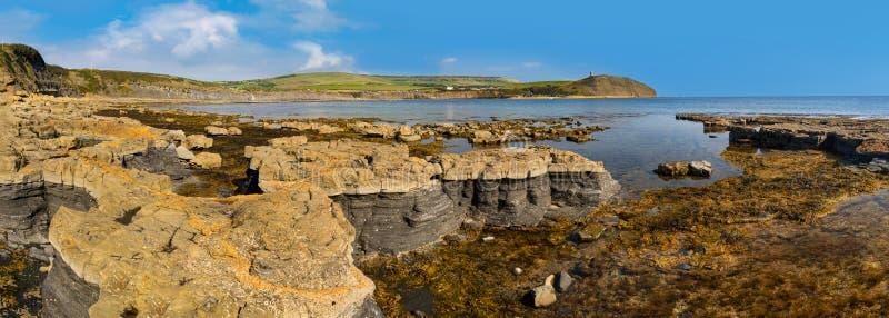 Το φωτεινό φως του ήλιου φωτίζει τη θάλασσα, τους βράχους και τους απότομους βράχους στο ιουρασικό κοβάλτιο στοκ εικόνα