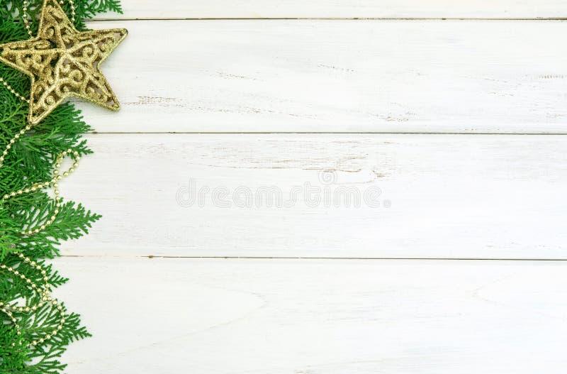 Το φύλλο πεύκων με την κίτρινη χρυσή διακόσμηση σφαιρών αστεριών και Χριστουγέννων στο λευκό ξύλινο πίνακα με το διάστημα, καλή χ στοκ εικόνες