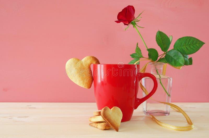 Το φλυτζάνι του coffe με τα μπισκότα δίπλα στο ένα κόκκινο αυξήθηκε στο βάζο στοκ εικόνες με δικαίωμα ελεύθερης χρήσης