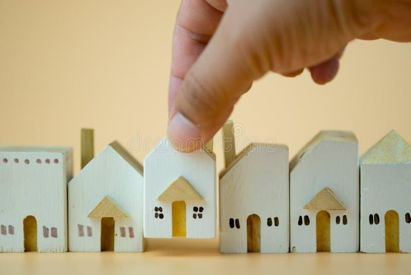 Το χέρι έβαλε το ξύλινο σπίτι στο πλήρες χωριό στοκ εικόνα με δικαίωμα ελεύθερης χρήσης