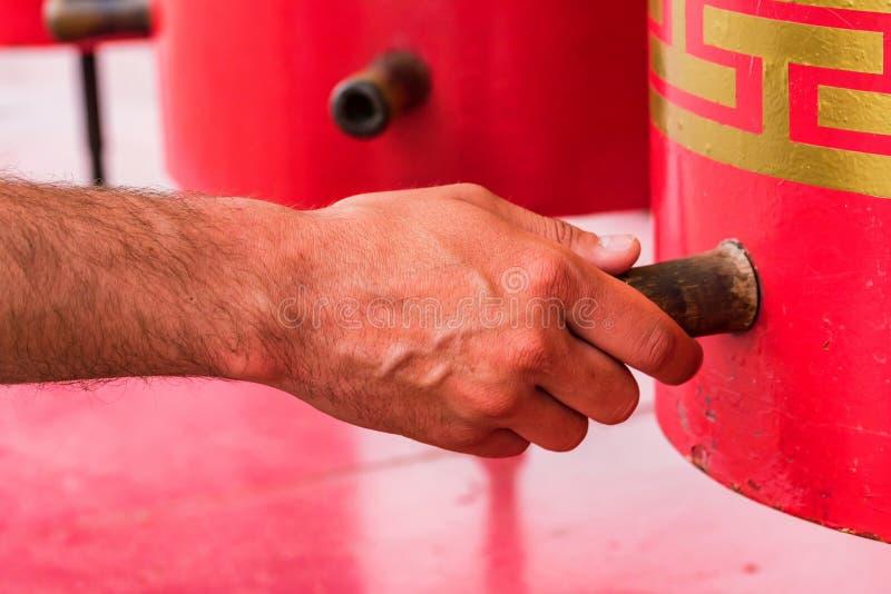 Το χέρι αγγίζει την κόκκινη βουδιστική ρόδα προσευχής στενή στοκ φωτογραφία