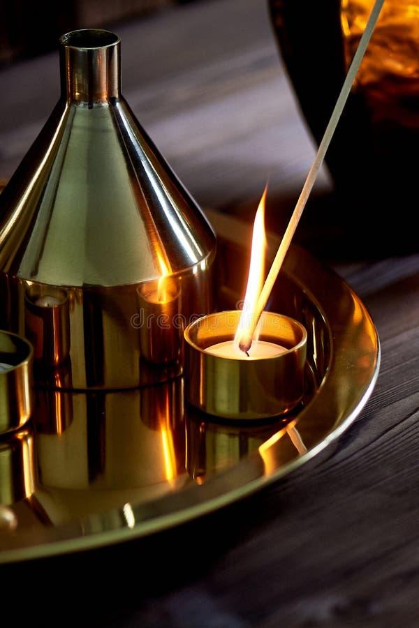 Το χέρι ανάβει ένα κερί με μια μακροχρόνια αντιστοιχία με μια φωτεινή φλόγα Το θερμό χρυσό γάμμα Άνεση βραδιού στοκ εικόνες με δικαίωμα ελεύθερης χρήσης