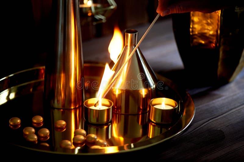 Το χέρι ανάβει ένα κερί με μια μακροχρόνια αντιστοιχία με μια φωτεινή φλόγα Το θερμό χρυσό γάμμα Άνεση βραδιού Πολλά βάζα στοκ φωτογραφία με δικαίωμα ελεύθερης χρήσης