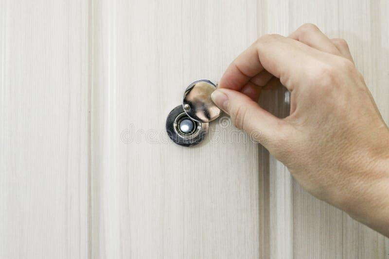 Το χέρι ανοίγει την κάλυψη ματάκι πόρτας πορτών στη μπροστινή πόρτα στοκ φωτογραφία με δικαίωμα ελεύθερης χρήσης