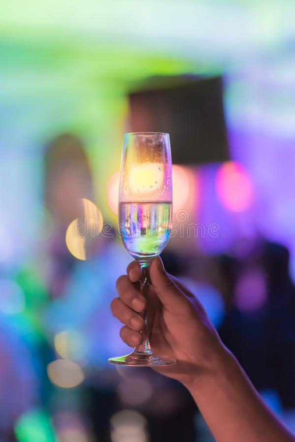 Το χέρι ατόμων κρατά ένα ποτήρι του άσπρου κρασιού στο κόμμα νύχτας στοκ εικόνα