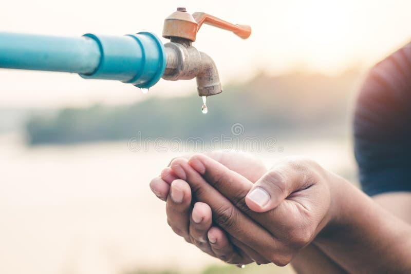 Το χέρι ατόμων περιμένει να πιει το νερό στη έλλειψη νερού στοκ φωτογραφία