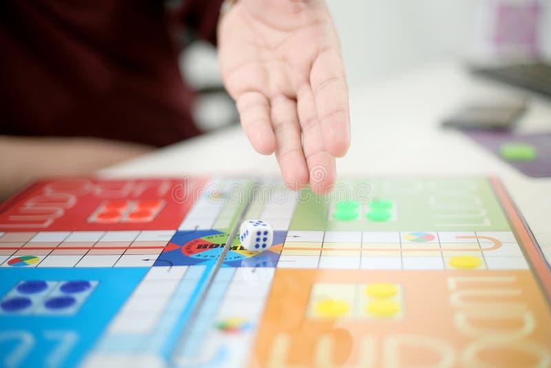 Το χέρι ατόμων ρίχνει χωρίζει σε τετράγωνα στο Ludo στοκ φωτογραφία