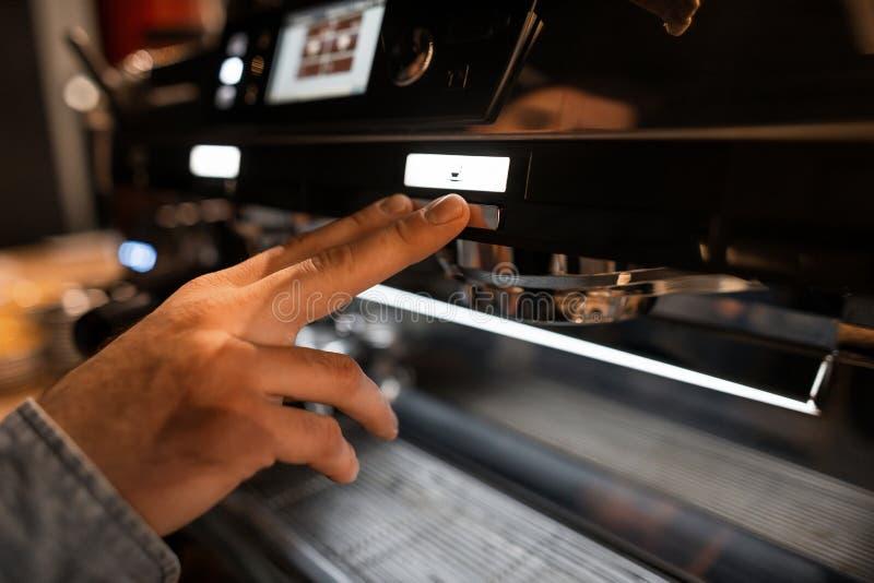 Το χέρι ατόμων Barista πιέζει το κουμπί έναρξης Bartender που κατασκευάζει τον καφέ σε μια μηχανή καφέ Κινηματογράφηση σε πρώτο π στοκ εικόνες