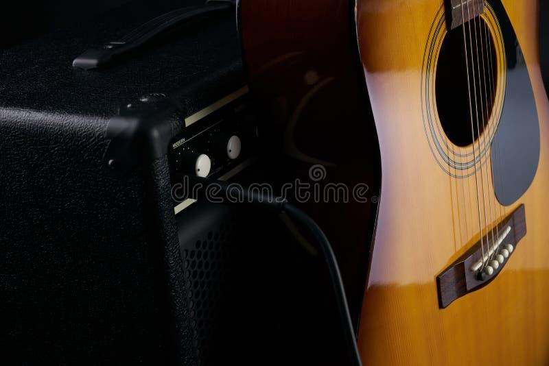 Το χέρι βάζει την ακουστική κλασσική κιθάρα στον ενισχυτή combo στοκ φωτογραφίες