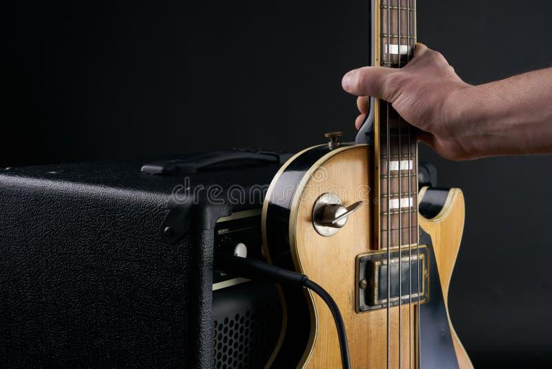 Το χέρι βάζει την εκλεκτής ποιότητας ξύλινη ηλεκτρική βαθιά κιθάρα στον ενισχυτή combo στοκ εικόνες με δικαίωμα ελεύθερης χρήσης