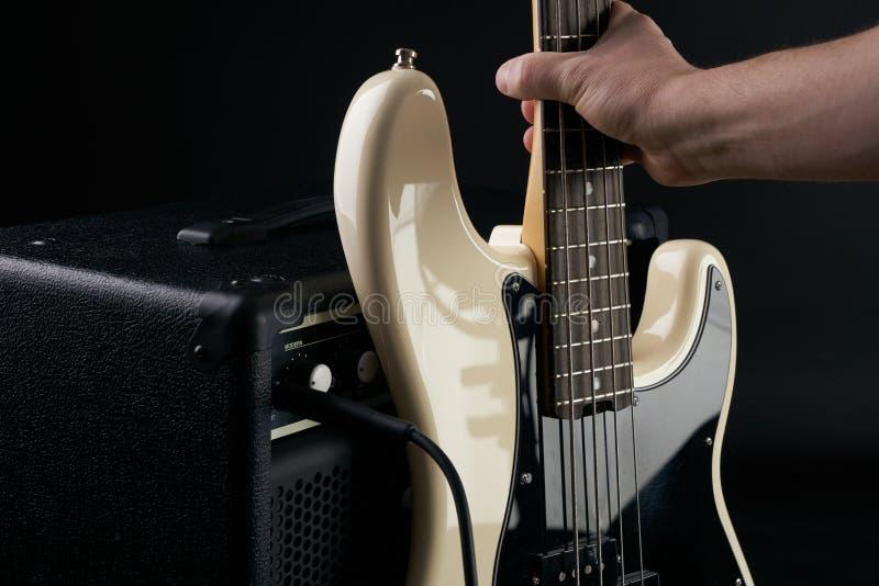 Το χέρι βάζει τη γραπτή ηλεκτρική βαθιά κιθάρα στον ενισχυτή combo στοκ εικόνα με δικαίωμα ελεύθερης χρήσης