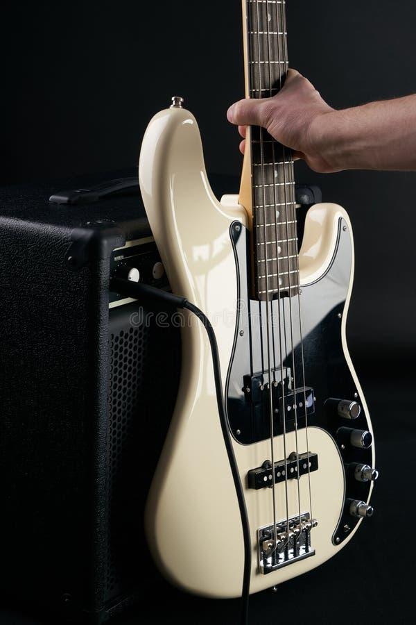 Το χέρι βάζει τη γραπτή ηλεκτρική βαθιά κιθάρα στον ενισχυτή combo στοκ φωτογραφία με δικαίωμα ελεύθερης χρήσης
