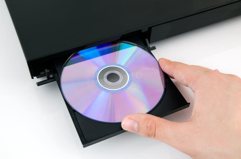 Το χέρι βάζει το δίσκο στο μηχάνημα αναπαραγωγής CD στοκ φωτογραφία
