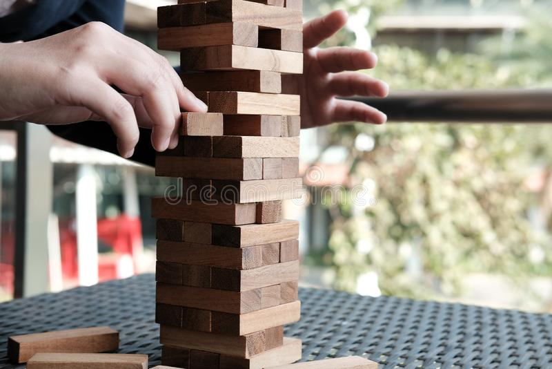 το χέρι βγάζει τον ξύλινο φραγμό από τον πύργο αύξηση, κίνδυνος & στρατηγική μέσα στοκ φωτογραφίες