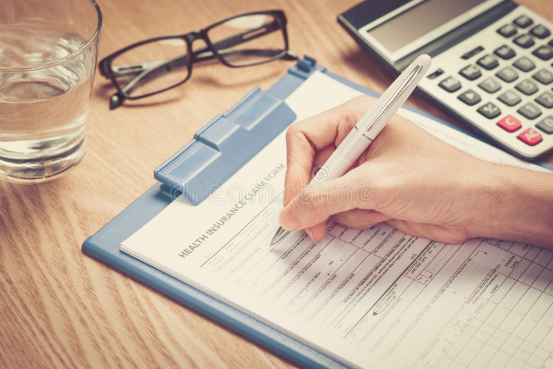 Το χέρι γράφει τη προσωπική πληροφορία στη μορφή αξίωσης ασφάλειας υγείας στοκ φωτογραφία