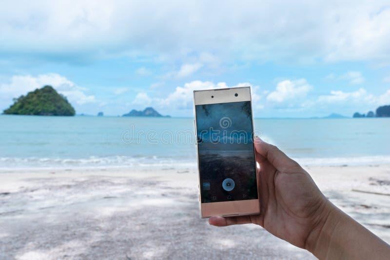 Το χέρι γυναικών παίρνει μια φωτογραφία του τοπίου θάλασσας με κινητό τηλέφωνο του υποβάθρου παραλιών θερινής θάλασσας στοκ εικόνες με δικαίωμα ελεύθερης χρήσης