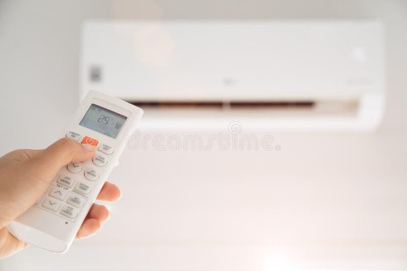 Το χέρι γυναικών που κρατά το μακρινό ελεγκτή κατεύθυνε στο κλιματιστικό μηχάνημα μέσα στο δωμάτιο και καθορισμένος στην περιβαλλ στοκ φωτογραφίες με δικαίωμα ελεύθερης χρήσης