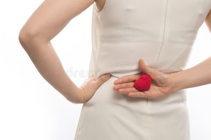 Το χέρι γυναικών που κρατά το κόκκινο σημάδι μορφής καρδιών πίσω επάνω το whtei στοκ εικόνα με δικαίωμα ελεύθερης χρήσης