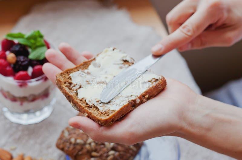 Το χέρι γυναικών τρίβει το βούτυρο στο κομμάτι του ψωμιού στοκ εικόνα με δικαίωμα ελεύθερης χρήσης