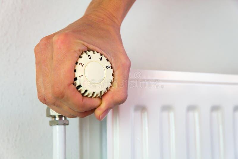 Το χέρι γυρίζει τη βαλβίδα θέρμανσης ανοικτή στο εσωτερικό στοκ φωτογραφία
