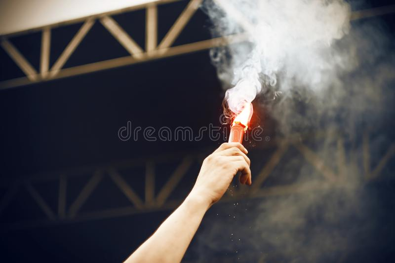 Το χέρι ενός ατόμου αυξάνεται στον αέρα με μια καίγοντας κόκκινη πυρκαγιά φλογών στοκ εικόνα με δικαίωμα ελεύθερης χρήσης
