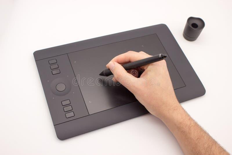 Το χέρι ενός ατόμου επισύρει την προσοχή stylus σε μια ταμπλέτα γραφικής παράστασης στοκ εικόνες