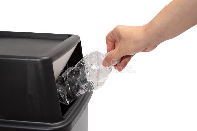 Το χέρι ενός ατόμου που ρίχνει ένα πλαστικό μπουκάλι σε ένα δοχείο απορριμμάτων στοκ εικόνες με δικαίωμα ελεύθερης χρήσης