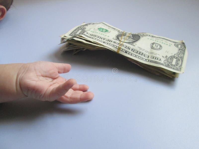 Το χέρι ενός μωρού που θέλει τα χρήματα όρου στοκ εικόνες