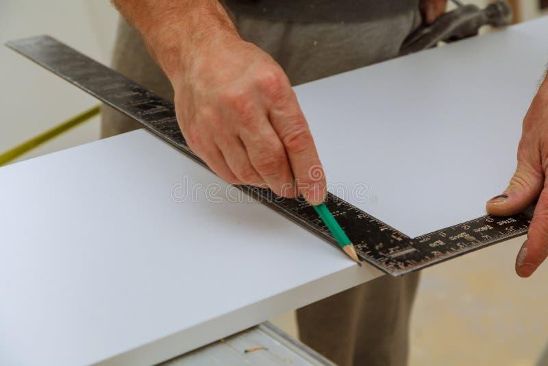 Το χέρι ενός ξυλουργού μετρά την απόσταση χρησιμοποιώντας ένα builder& x27 τετράγωνο και σημάδια του s στοκ εικόνες