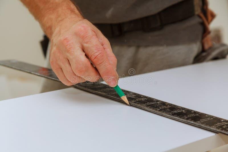 Το χέρι ενός ξυλουργού μετρά την απόσταση χρησιμοποιώντας ένα builder& x27 τετράγωνο και σημάδια του s στοκ φωτογραφία
