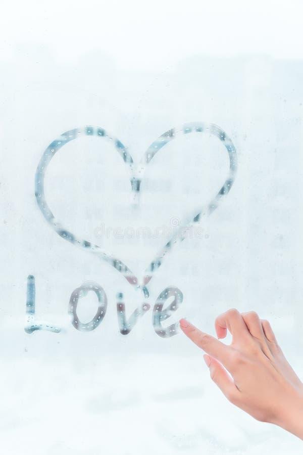 Το χέρι επισύρει την προσοχή την καρδιά αγάπης στο κρύο θόλωσε υπόβαθρο παραθύρων, εικόνα κινηματογραφήσεων σε πρώτο πλάνο στοκ εικόνα με δικαίωμα ελεύθερης χρήσης