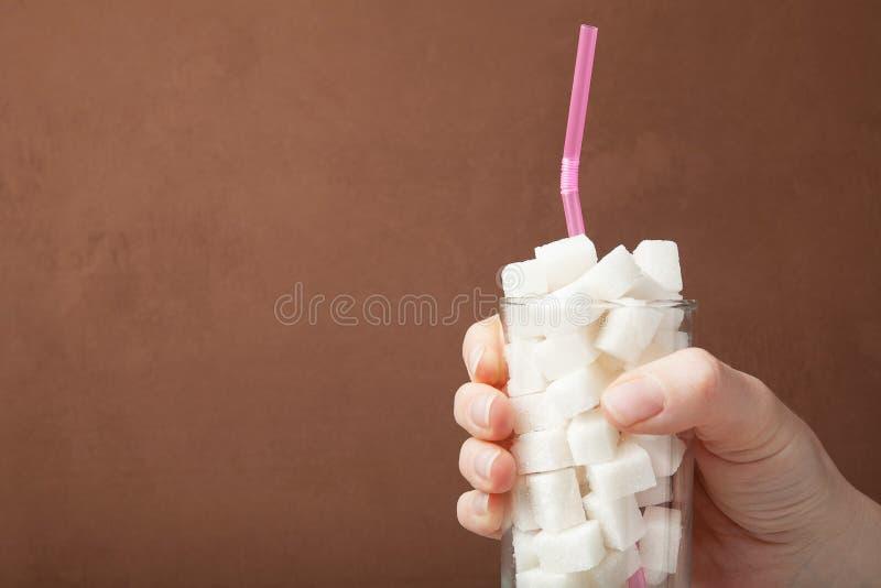 Το χέρι και το γυαλί με τη ζάχαρη πίνουν, η έννοια της υπερβολικής κατανάλωσης ζάχαρης στη διατροφή r στοκ φωτογραφία με δικαίωμα ελεύθερης χρήσης