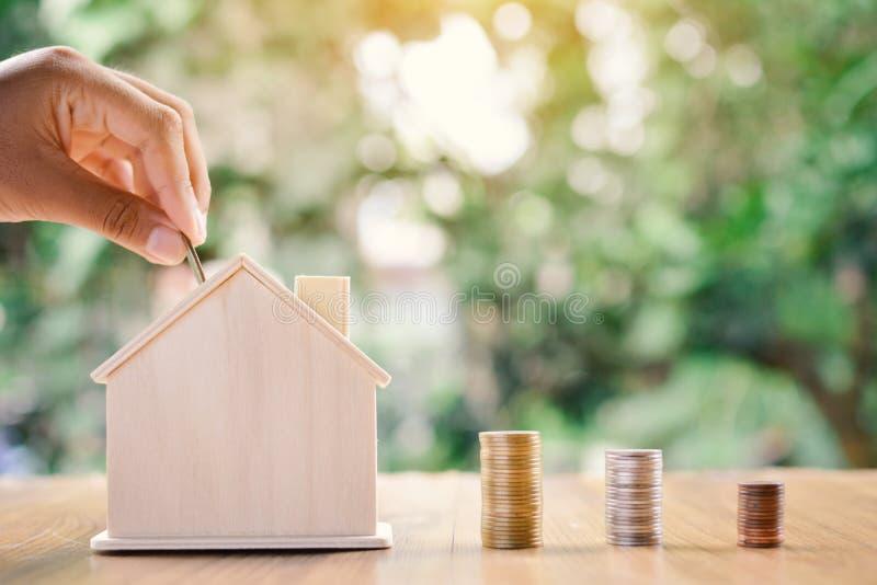 Το χέρι και η έννοια νομισμάτων κερδίζουν χρήματα για το σπίτι μου στοκ φωτογραφίες