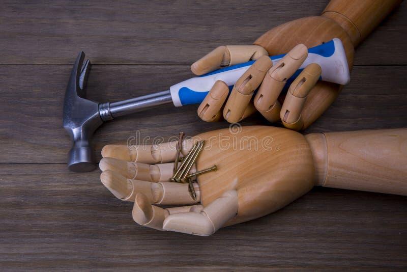 Το χέρι κρατά ένα σφυρί και μερικά καρφιά στοκ φωτογραφίες