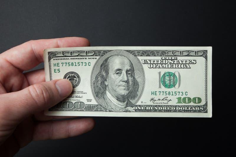 Το χέρι κρατά 100 δολάρια σε ένα μαύρο υπόβαθρο Η έννοια της αγοράς και της πώλησης στοκ εικόνες