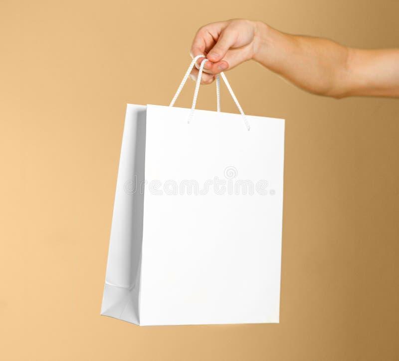 Το χέρι κρατά μια άσπρη τσάντα δώρων στοκ φωτογραφία