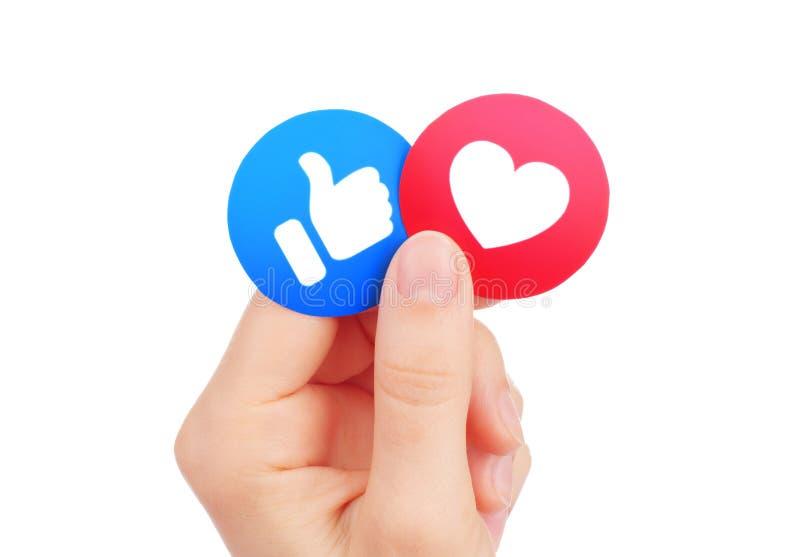 Το χέρι κρατά νέο Facebook όπως και τις με κατανόηση αντιδράσεις Emoji αγάπης διανυσματική απεικόνιση