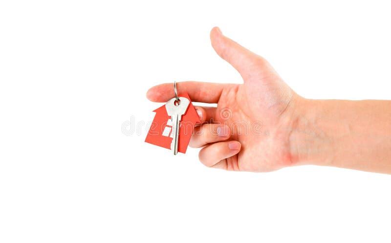Το χέρι κρατά τα κλειδιά με το κόκκινο σπίτι keychain Αγορά στοκ εικόνα