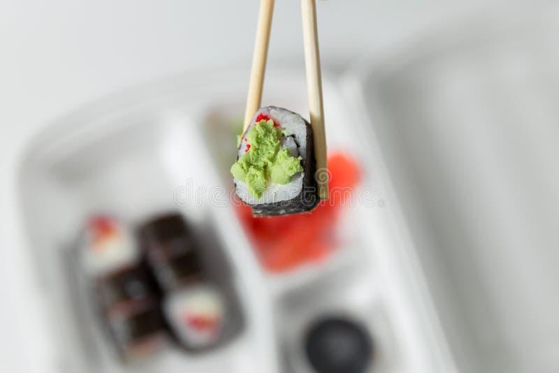 Το χέρι κρατά το ρόλο με chopsticks, ρόλοι, σούσια chopsticks, πιπερόριζα, σάλτσα σόγιας στην παράδοση εμπορευματοκιβωτίων στοκ εικόνα