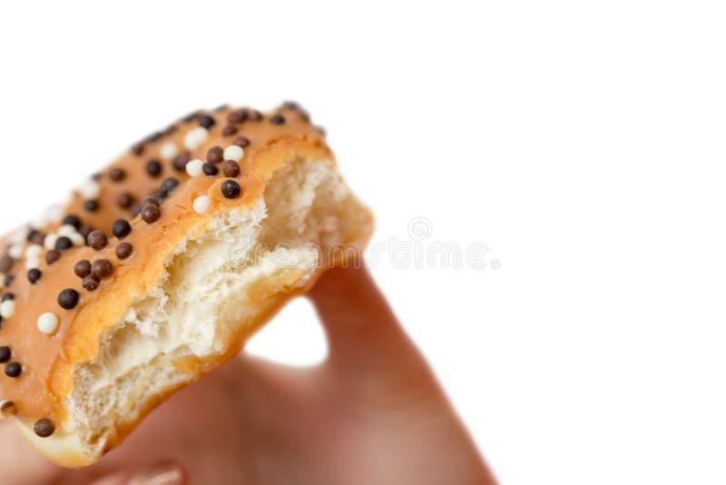 Το χέρι κρατά ότι doughnut με ψεκάζει απομονωμένος στο άσπρο υπόβαθρο στοκ φωτογραφία με δικαίωμα ελεύθερης χρήσης