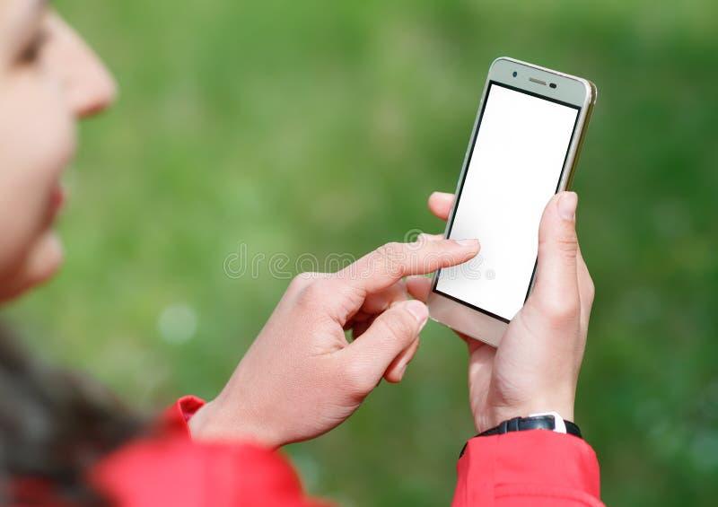 Το χέρι κρατά ότι το smartphone για παρουσιάζει και αγγίζει με την άσπρη οθόνη είναι υπαίθριο στοκ εικόνες