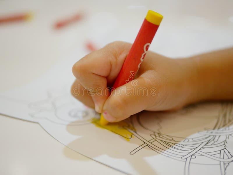Το χέρι λίγου μωρού που κρατά ένα κραγιόνι και σχεδιάζει τη ζωγραφική στοκ φωτογραφία με δικαίωμα ελεύθερης χρήσης