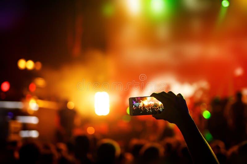 Το χέρι με ένα smartphone καταγράφει το φεστιβάλ ζωντανής μουσικής, ζωντανή συναυλία, παρουσιάζει στη σκηνή στοκ εικόνα με δικαίωμα ελεύθερης χρήσης